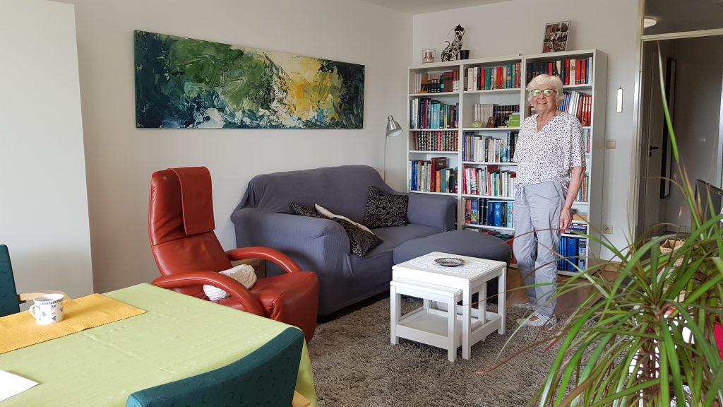 Enkele kopers van de schilderijen van Veerle Smet: foto van Huguette in haar woonkamer met het schilderij van Veerle Smet dat zij kocht aan de muur